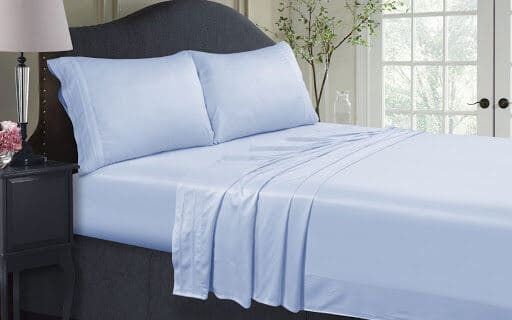 Cama con sábanas de satén de algodón. Brillo, lustre, lujo, suavidad, seda.