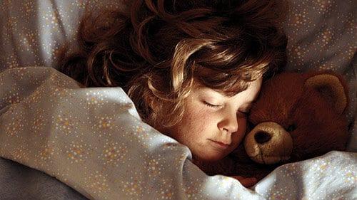 Niña durmiendo en sábanas infantiles